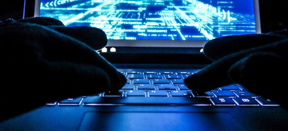 Cybercriminal with hands in gloves hacking into a system