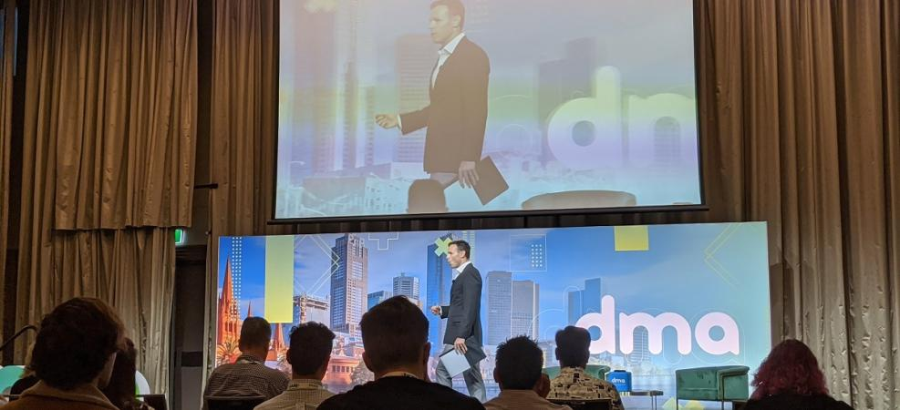 MC walking across stage at Digital Marketers Australia Conference 2020