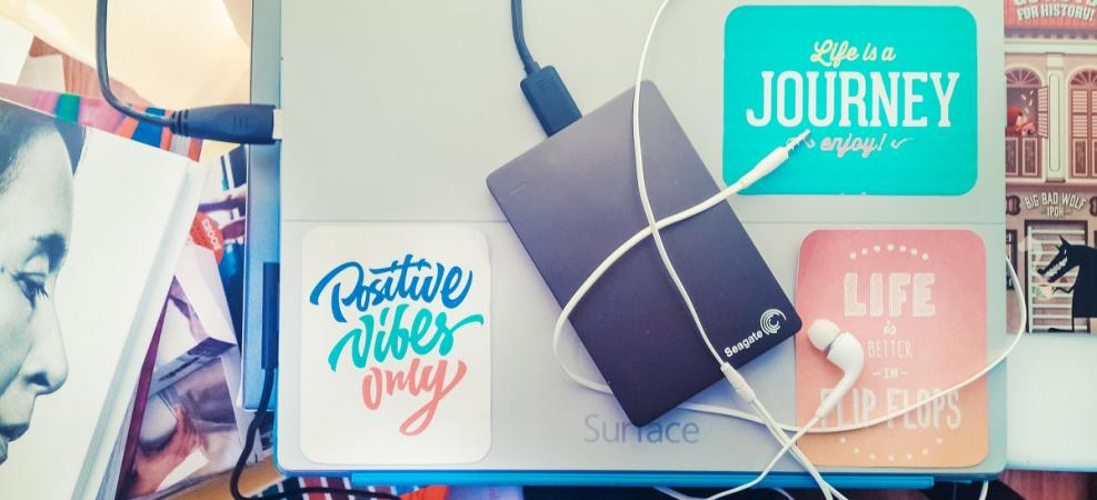 Hard drive and headphones on top of Surface tablet with inspirational images/messages surrounding it