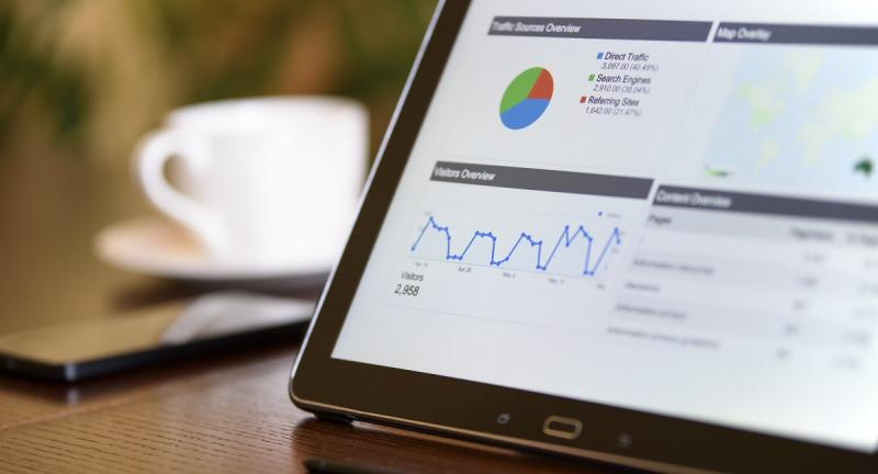 Web analytics on black tablet computer next to phone and coffee on table