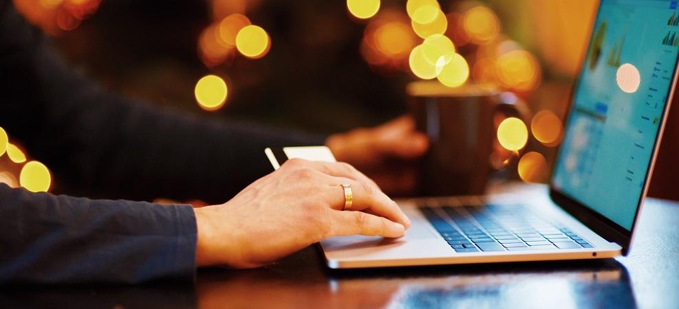 Person on laptop, bright lights in background