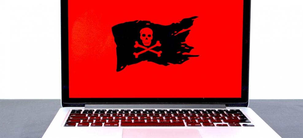 Laptop computer with skull and crossbones on screen, indicating danger