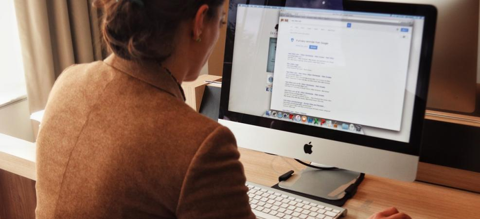 Woman in brown jacket with back to camera completing an online search on computer