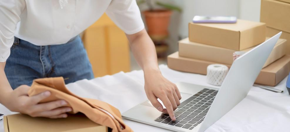 Woman on laptop near boxes on table while packaging up an online order