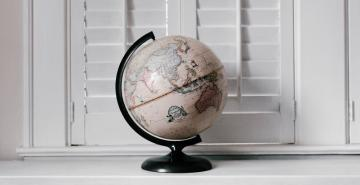 World globe on white bench in front of shutters