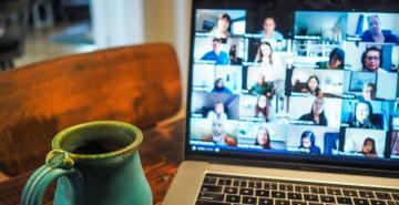 Laptop screen showing various participants on screen attending online video meeting