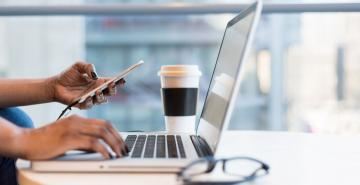 Person looking at phone with laptop computer on desk near glasses and a cup of coffee