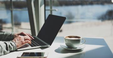 Person typing on laptop with black screen and coffee on desk nearby