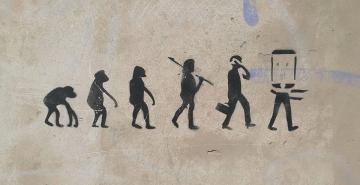 Cave drawing of species evolving from an ape to a mobile device