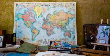 Map of world leaning on wall of study on desk with books, pencils and paint